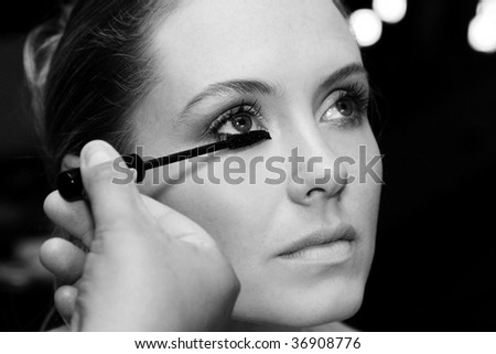 Bride sitting patiently while make-up is being applied