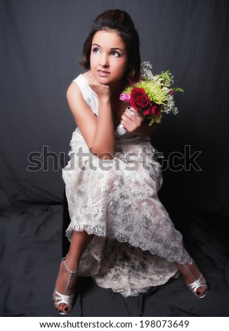 Bride sitting with a bouquet in her hands - stock photo