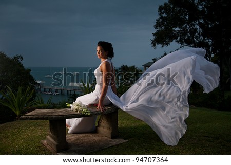 Bride sitting with dress blowing in the wind behind her