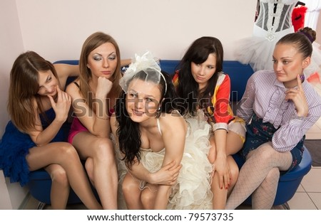 Bride sitting with envious girlfriend in professional fashion designer studio - stock photo