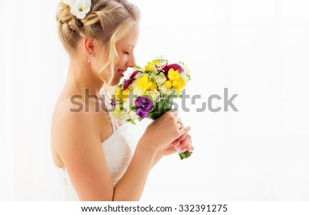 Bride smelling her wedding bouquet - stock photo