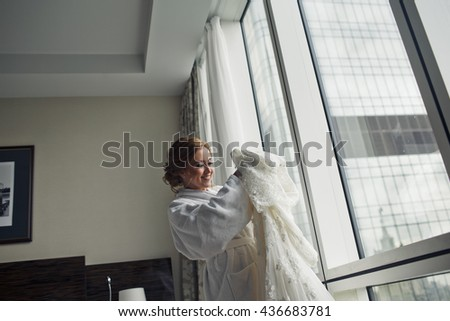 Bride smiles standing in a hotel room with rich wedding dress in her arms - stock photo