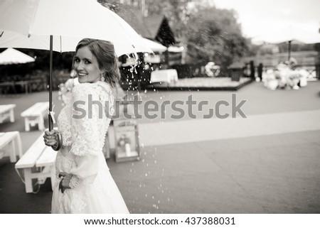 Bride smiles standing in the rain under an umbrella - stock photo