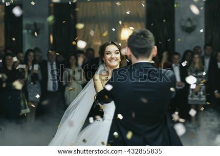 Bride smiles while dancing in the rain of confetti - stock photo