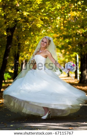 Bride spinning in a white dress in the middle of the autumn party committee in the yellow leaves. - stock photo