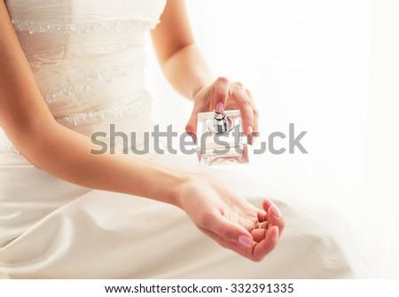 Bride spraying perfume  - stock photo