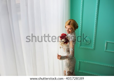 Bride standing by the window with flowers in her hand