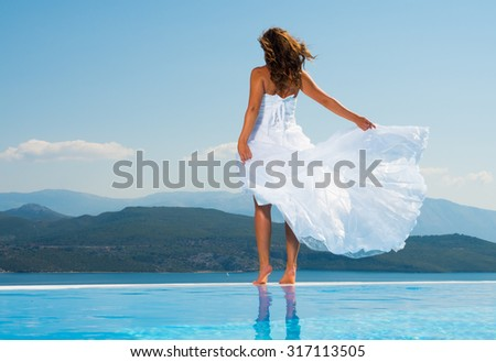Bride standing on the edge on the infinity pool in Greece - stock photo