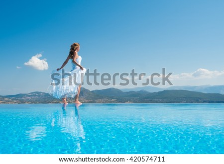 Bride standing on the edge on the infinity pool in Santorini Greece