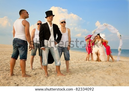 Bride standing with bridesmaids under archway on beach and waiting for her groom - stock photo