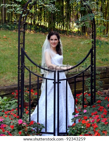 Bride stands behind a black metal arch and gate.  Red flowers bloom at her feet and she glows with a happy smile. - stock photo