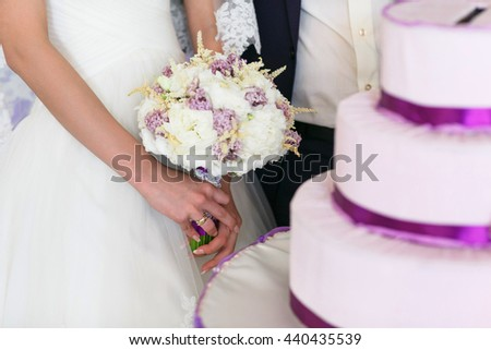 Bride stands behind a wedding cake holding a bouquet in her hands