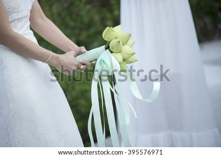 Bride throwing flowers with green weddings - stock photo