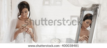 Bride using mobilephone, writing text message.