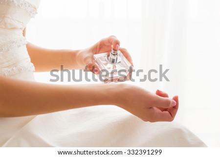 Bride using perfume  - stock photo