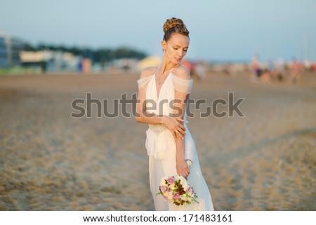 Bride walking along sea coast wearing beautiful wedding dress - stock photo