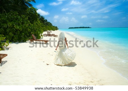 bride walking on the beach - stock photo
