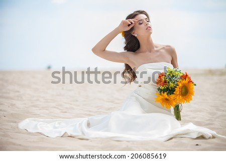Bride walking on the sea coast wearing beautiful wedding dress with bouquet