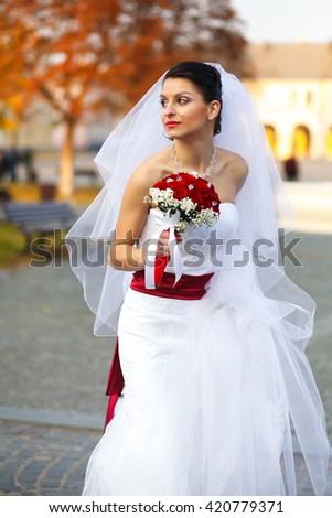 Bride walks around an autumn city holding a skirt of wedding dress in her arm - stock photo