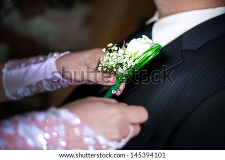 bride wears a flower in his button-hole - stock photo
