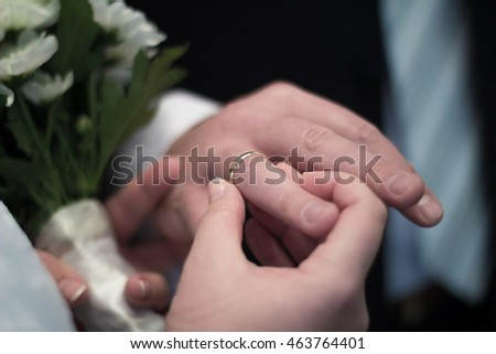 Bride wears ring to bridegroom's finger. Close up shot. There are blurred flowers on background.