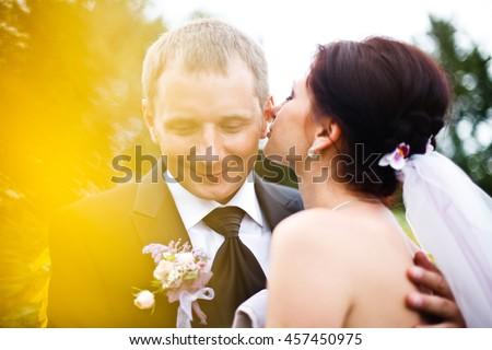 Bride whispers something on groom's ear - stock photo