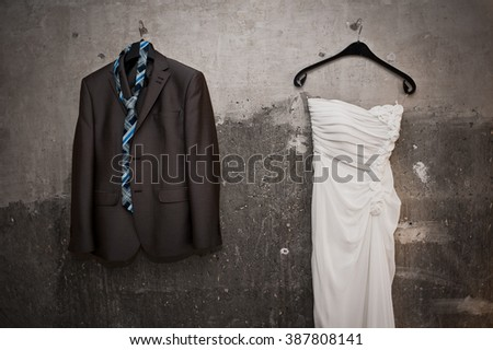 Bride white wedding dress and groom black suit with tie hanging on the textured grunge wall.