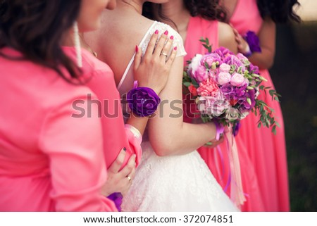bride with a bouquet and bridesmaids in identical dresses of pink color - stock photo