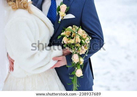 bride with a bouquet in the arms of the groom - stock photo