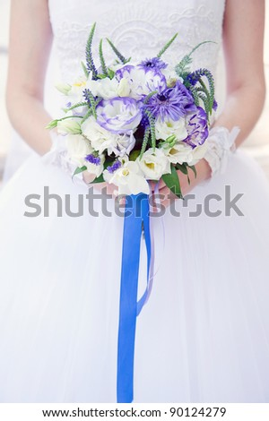 Bride with a wedding bouquet with white and violet flowers tied with blue ribbon, soft focus. - stock photo