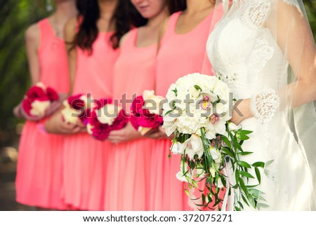 bride with a white bouquet and bridesmaids in a pink dress - stock photo