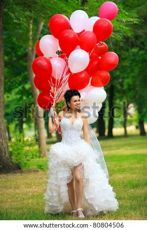 Bride with balloons in park - stock photo