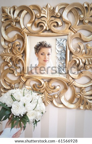 bride with bouquet of flowers looking at herself in the antique mirror with golden flower patterns