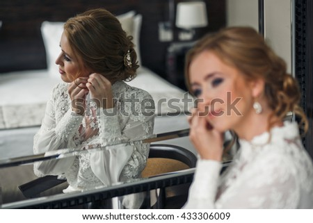 Bride with curly hair adjusts an earring sitting behind a mirror - stock photo