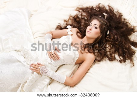 Bride with curly long hair lying over white. High angle view. Fashion wedding shoot. - stock photo