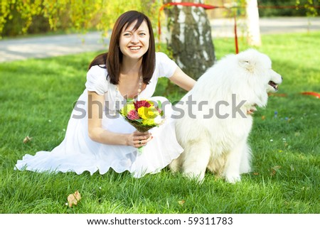 Bride with dog Samoyed sitting on the grass