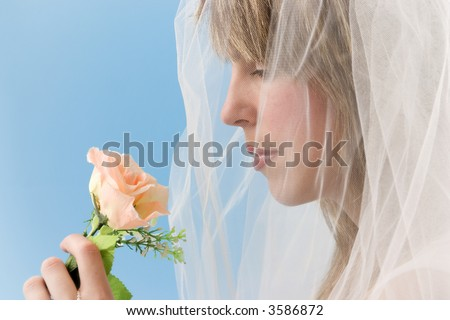Bride with flower on blue background - stock photo