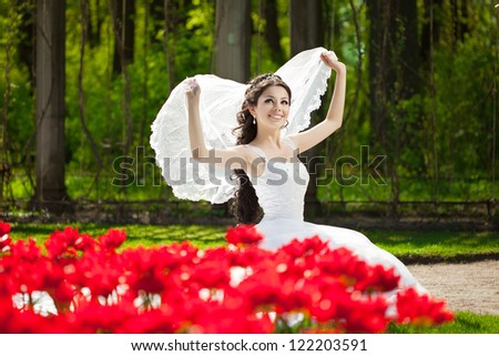 Bride with flowers outdoors - stock photo