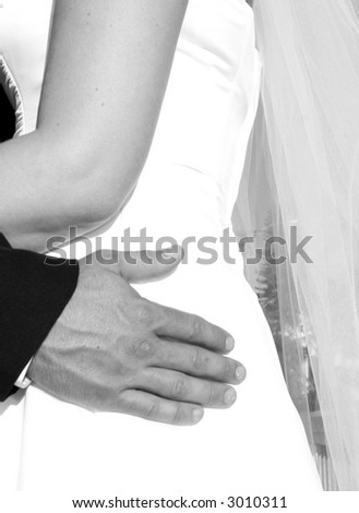 Bride with groom holding onto waist in black and white - stock photo