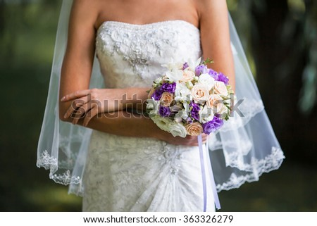 bride with veil holding Wedding bouquets on wedding ceremony