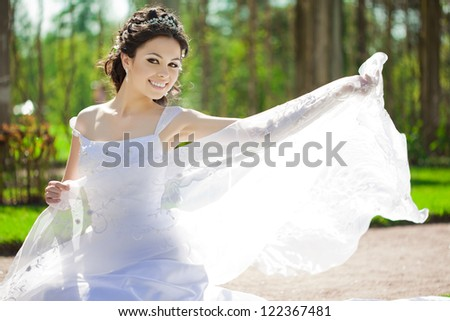 Bride with veil outdoors - stock photo