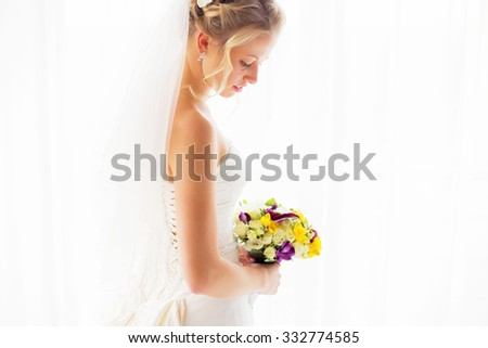 Bride with veil standing by the window  - stock photo