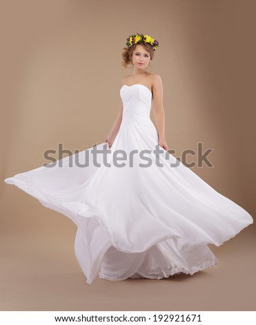 Bride with Vernal Wreath of Flowers in Flying Wedding Dress - stock photo