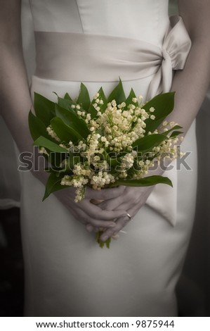 Bride with wedding bouquet made from lily of the valley. - stock photo