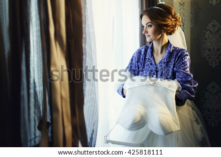Bride with wedding dress in her arms looks thoughtful - stock photo