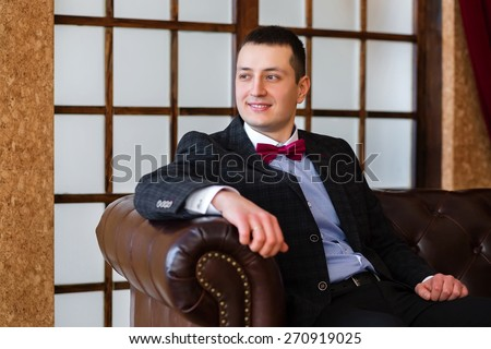 Bridegroom is sitting on a leather sofa and looking away - stock photo