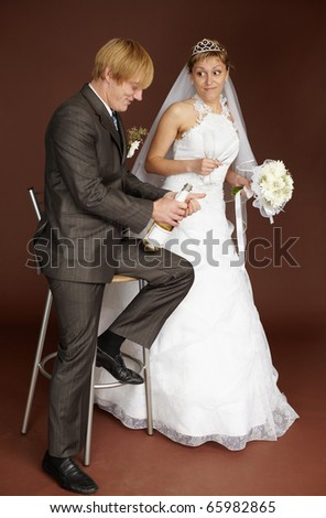 Bridegroom opens champagne wine on a brown background - stock photo