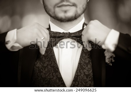Bridegroom preparing for the wedding, corrects a beautiful bow-tie. Black and white - stock photo