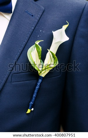 Bridegroom wearing in dark blue formal suit with elegant boutonniere from Calla Lily flower and Hosta leaves. The flower and leaves tied with a ribbon. Close-up photo of the beautiful boutonniere. - stock photo