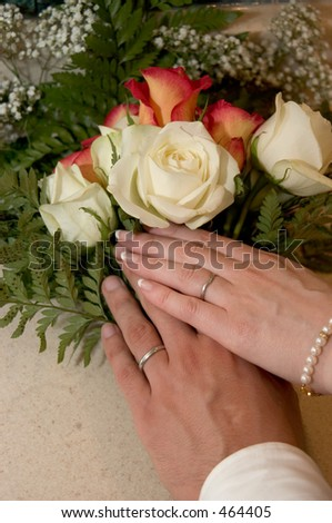 Brides and groom hands showing wedding rings on top of a bouquet. - stock photo